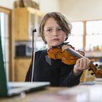six year old boy playing violin having a remote vi ARFWSNB